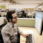 male, glasses, grey shirt, beard, monitor, cubicle,